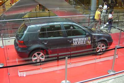 In het midden van de gang van het winkelcentrum Arkaden staat de VW Golf van Paus Benedictus XVI.