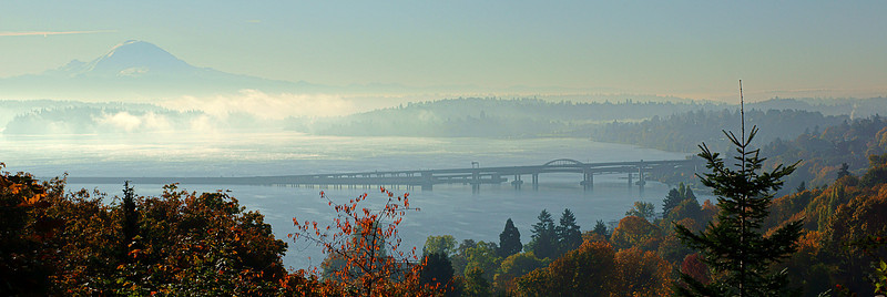 This is the I-90 bridge across Lake Washington on an early fall morning as the fog is burnt off revealing Mt. Rainier.