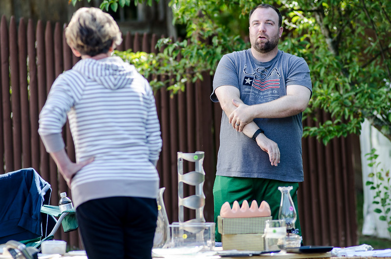 Travis Ross speaks with customers during the community wide yard sale in Fitchburg on Saturday. SENTINEL & ENTERPRISE / Ashley Green