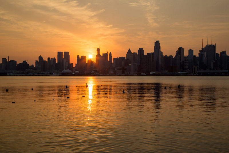 The sun rises behind the skyscrapers of New York