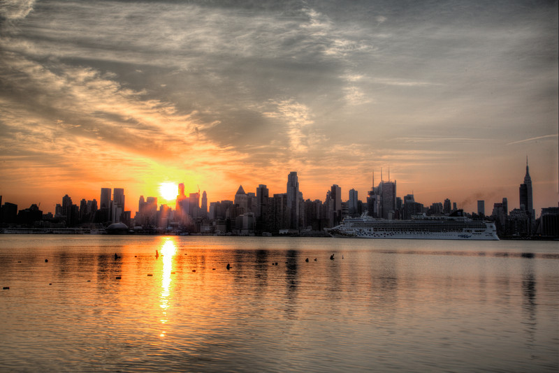 The cruise ship Norwegian Gem arrives in New York at sunrise as the sun rises behind the skyline of Manhattan