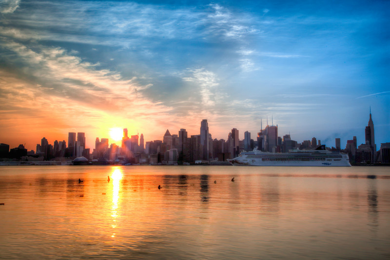 The cruise ship Norwegian Gem arrives in New York at sunrise as the sun comes up behind the skyline of Manhattan