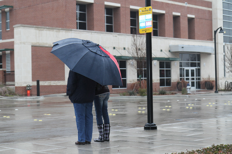 Unknown spectators in Garland waiting for Garland's annual NAACP MLK parade with umbrella.