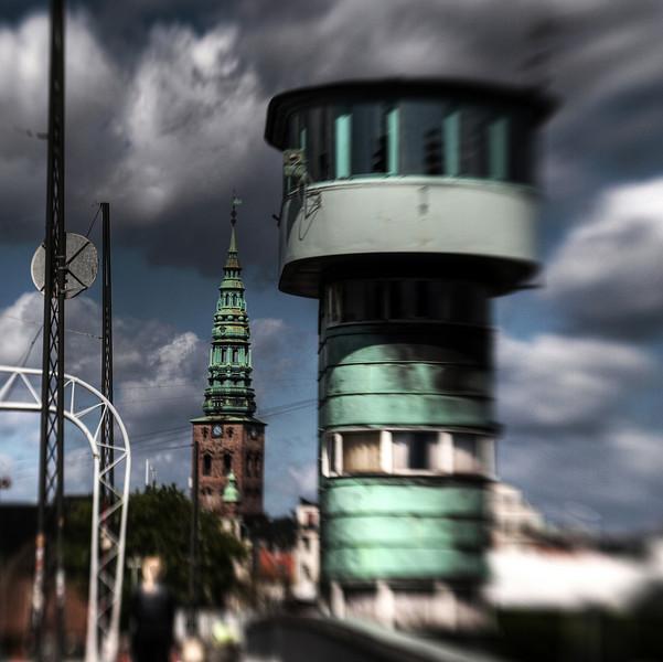 Control Towers.<br /> In front the control Tower for a bascule bridge, at the back the tower of Saint Niklas Church.<br /> Nikolaj Kirke set fra Knippelsbro, København, Danmark.<br /> Fotograferet med en Lensbaby.