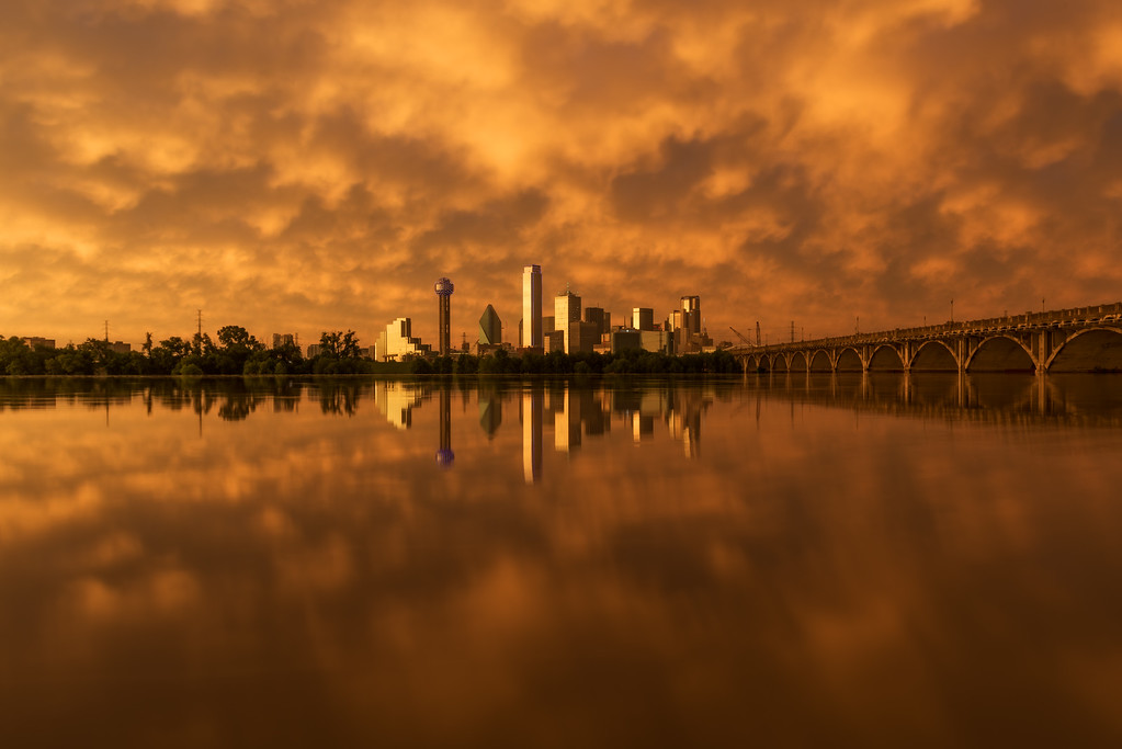 The Dallas, Texas skyline reflects in a flooded Trinity River at sunset on May 25, 2015.