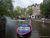 An Amsterdam canal boat maneuvers around a corner