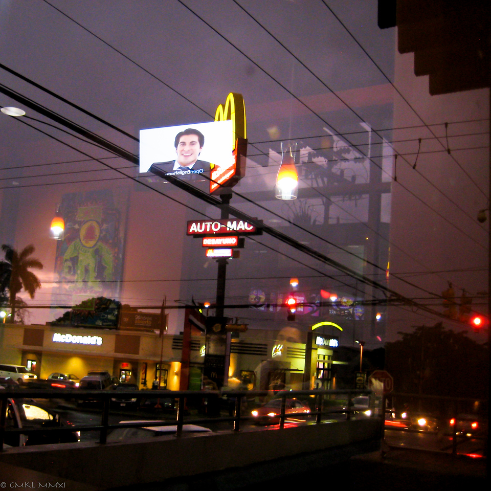 Super imposed with tripple reflections - a busy intersection in Alajuela