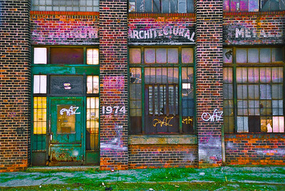 """1974 Franklin St.,"" Rivertown District, Detroit, 2003.    Fresh grass clippings on the sidewalk in front of what once was the Aluminum Architectural Metals company.  An abandoned historic building that continues to be photographed today."