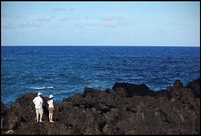 Tourists standing on black lava rocks  Waianapanapa State Park, Maui, Hawaii