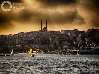 A view from the shore of the Bosphorus in Istanbul as the sun and clouds mingle above.