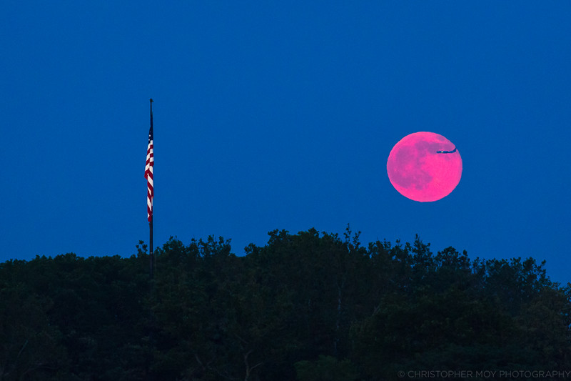 A plane flying by the Strawberry Moon