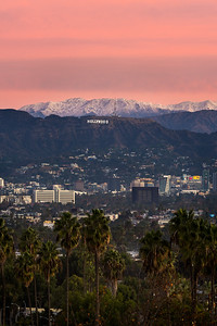 Hollywood sign with palm trees and snow capped mountains at sunrise
