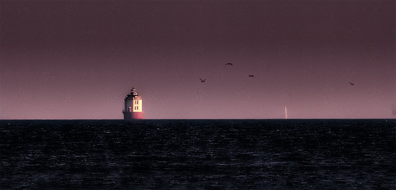 The Lighthouse off Point No Point with sailboat and birds. Chesapeake Bay, Maryland. November 19th, 2011. <br /> Taken at sunrise from the pier at Lookout Point, at a distance of 6 miles to the south.