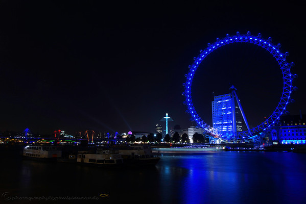The London Eye showcasing the blue lighting that reflects across the Thames with the excitement of the funfair ride nearby