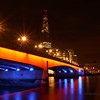 The striking orange and blue lighting up London Bridge with the enormous structure of The Chard in the distance