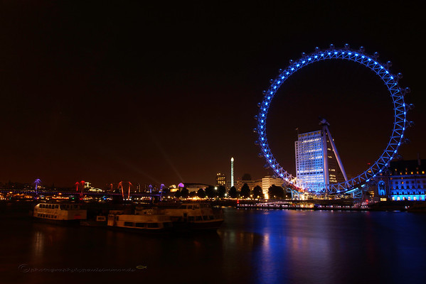 The London Eye standing in its full glory with soft reflected light across the Thames