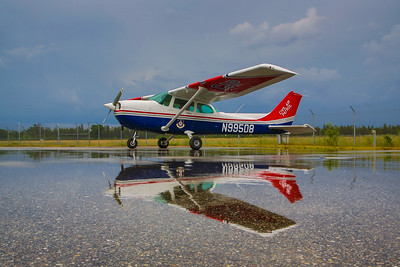A Cessna 172 sitting on the ramp at KGOV after a rainstorm showing the reflection of the aircraft in the water.