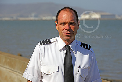 ALCPILOT 00006 Ed McDemott, an ASTAR Air Cargo DC-8 co-pilot, on his way to work at SFO, stands at a sea wall with SFO in the background, by Peter J Mancus
