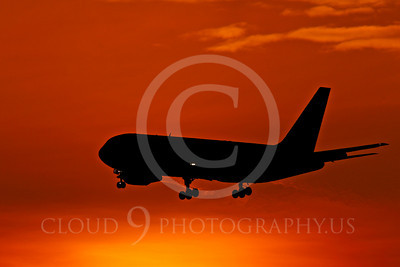 ALPSIL 0000I A flying Boeing 767 airliner is silhouetted against an early morning orange skyf, by Peter J Mancus