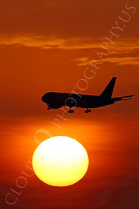 ALPSUN 00001 A Boeing 767 airliner flys pass a rising sun, by Peter J Mancus