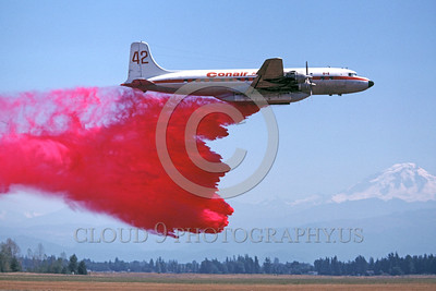 FF-DC-7 00006 A flying Douglas DC-7 Conair drops anti-fire retardant Canada 9-1977 fire fighting airplane picture by Peter B Lewis