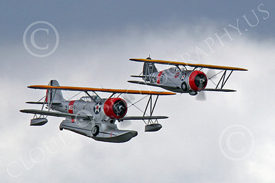 WB - Grumman J2F Duck 00034 A USMC Grumman J2F Duck float plane warbird in formation with a Grumman F3F biplane fighter warbird, by Peter J Mancus