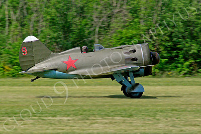 WB - Polikarpov I-16 00003 Side view of a World War II era Polikarpov I-16 warbird fighter plane in Soviet markings taking off from a grass field, by Stephen W D Wolf