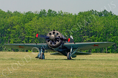 WB - Polikarpov I-16 00007 A quarter front taxi view of a World War II era Polikarpov I-16 warbird fighter plane in Soviet markings on a grass field, by Stephen W D Wolf