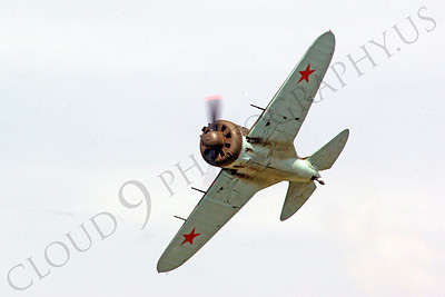 WB - Polikarpov I-16 00004 A World War II era Polikarpov I-16 warbird fighter plane in Soviet markings banks in flight, by Stephen W D Wolf