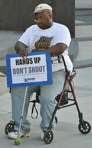 """African-American man sitting in wheelchair holding """"Hands Up Don't Shoot"""" sign."""