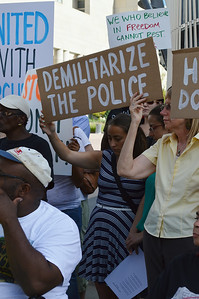 """Two women hild sign """"Demilitarize The Police"""", other protesters around them with signs."""