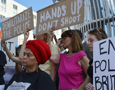 African-American woman wearing red turban, behind her, two women with signs about demilitarizing the police.