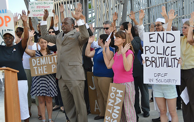 Demonstrators holding hands up in the air, one hold sign about police brutality.