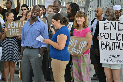 """Group of demonstrators singing, one holds """"End Police Brutality"""" sign."""