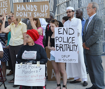 Two women holding signs about police brutality and police murder, one woman wearing red turban, Muslim Iman dressed in white and other demonstrators with signs, behind them.