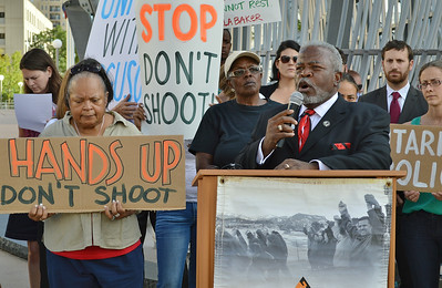 """African-American man in suit, speaks from podium using microphone, next to him, demonstrator with """"Stand Up Don't Shoot"""" sign, other protesters behind him."""