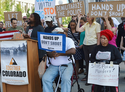"""African-American man standing at podium, singing, other around him with signs and American flag, one sign says """"Hands Up Don't Shoot"""", other signs about police."""