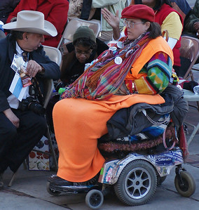 Woman in wheelchair and man in cowboy hat listen to speakers at MLK Day rally in Denver.