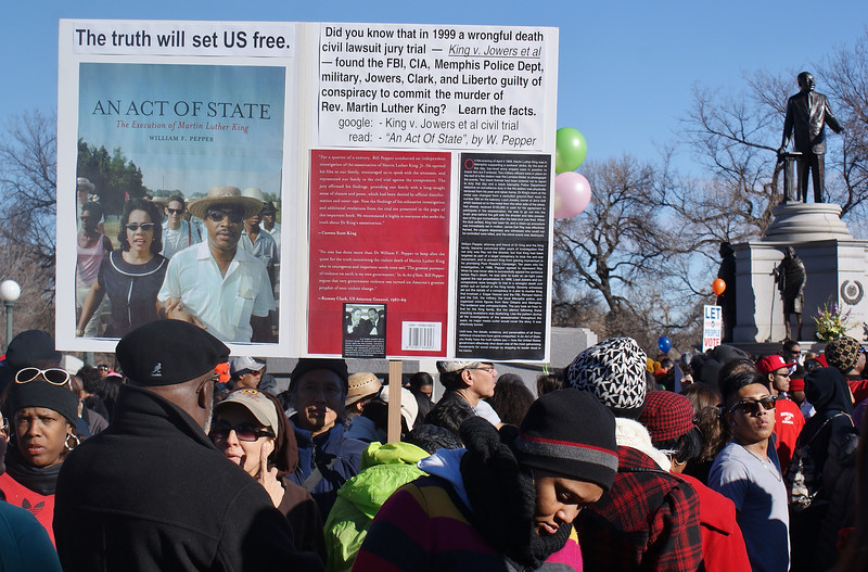 Man displays sign about MLK assasination near MLK statue.