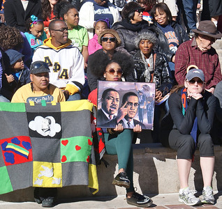 African-American woman holding painting of MLK and Malcolm X and another woman holding quilt, listen to speakers at MLK Day rally in Denver.