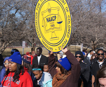 African-American woman holds a large NAACP sign during the MLK Day march in Denver.