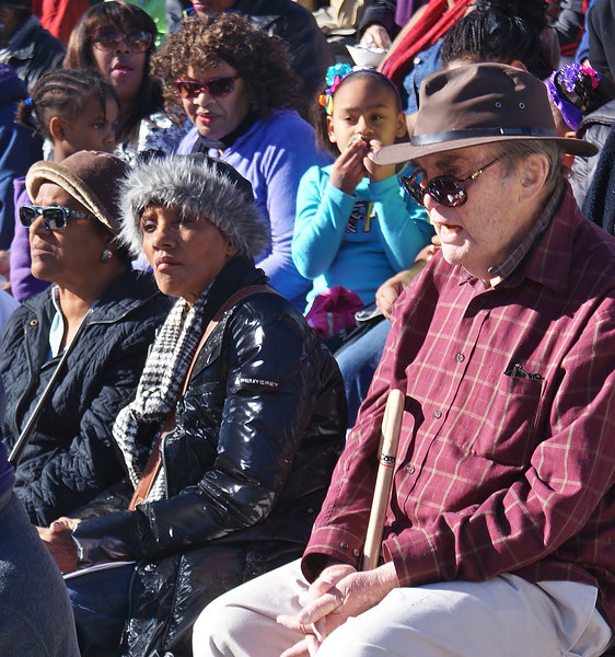 Older man with cane listens to speakers at MLK Day rally in Denver.