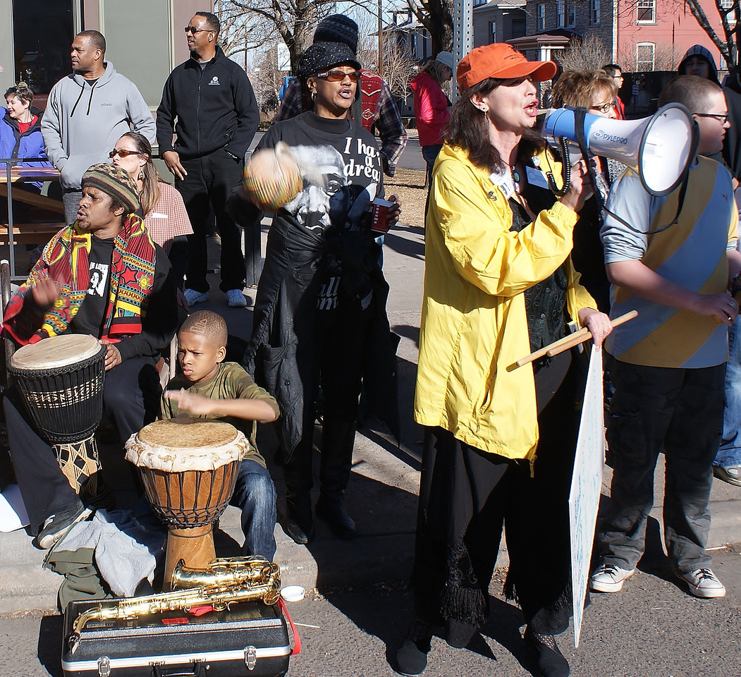 Group of drummers perform on the MLK Day parade route  as woman speakes with bullhorn.