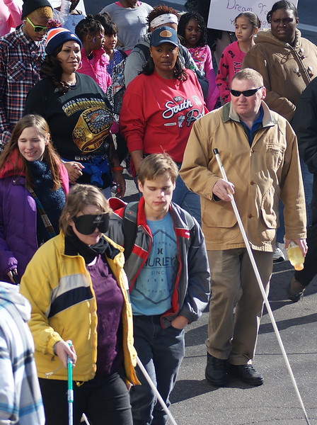 Blind people with canes march in the MLK Day parade in Denver.