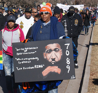 African-American man marches with sign with image of Martin Luther King and his prisoner number from the Birmingham, Al jail, at MLK Day parade in Denver.