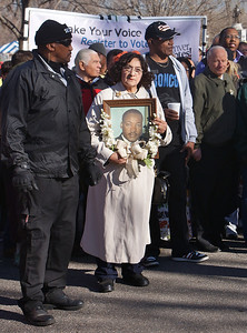 Woman holding framed picture of Martin Luther King adorned with flowers, waits for the Denver MLK Day march to begin.
