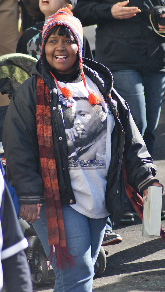 Smiling African-American woman wearing Martin Luther King shirt,  marching in MLK Day parade in Denver.