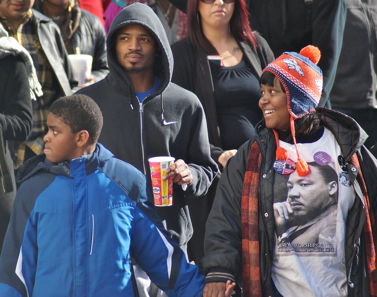 Smiling African-American woman wearing Martin Luther King shirt, holding sons hand while marching in MLK Day parade in Denver.