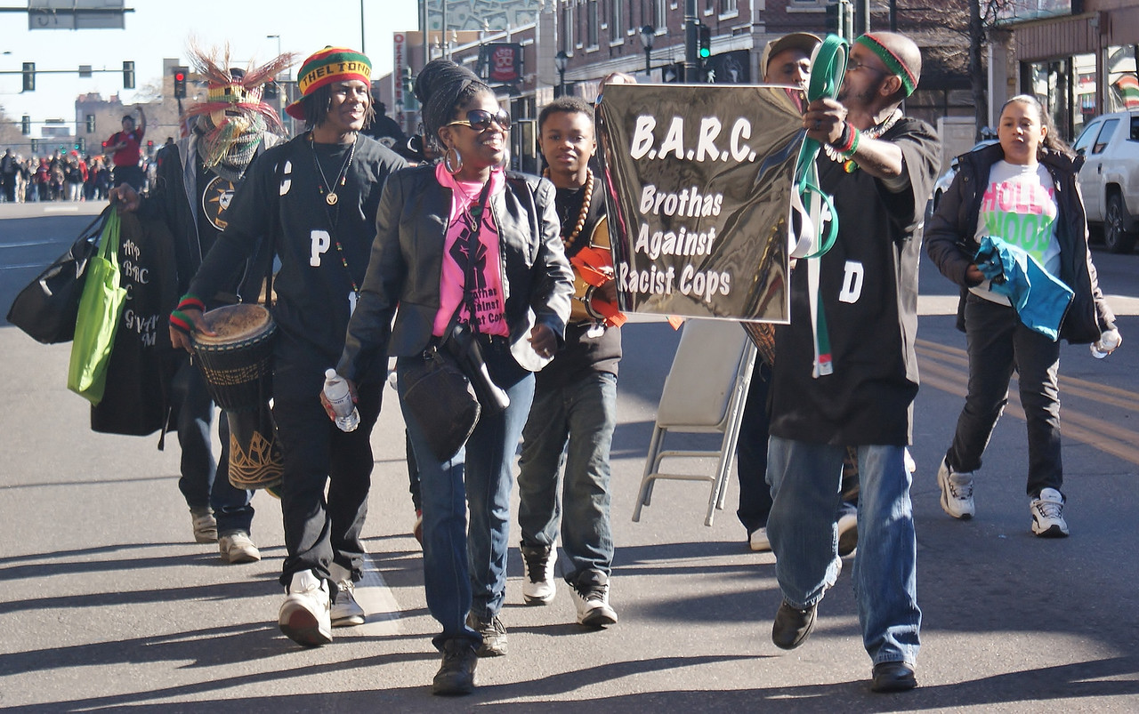 """Members of """"Brothas Against Racist Cops"""" display banner, while marching in MLK Day parade in Denver."""