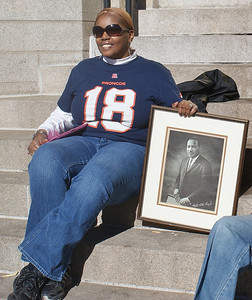 African-American woman wearing Denver Broncos #18 jersey, sitting on step with framed picure of Martin Luther King, aloon the route of MLK Day parade in Denver.